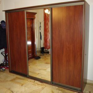 Niska szafa w przedpokoju z drzwiami suwanymi , drzwi wykonane z płyty i lustra srebrnego w okuciach aluminiowych