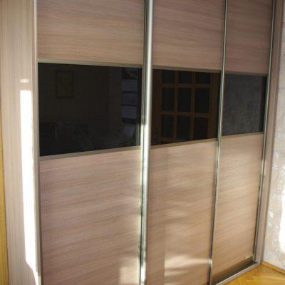 Drzwi przesuwne w szafie na wymiar, połączenie płyty i czarnego szkła lacobel