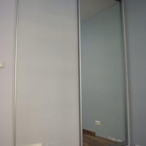 Drzwi przesuwne w szafie wnękowej, połączenie płyty laminowanej i lustra srebrnego