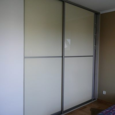 Szafa wnękowa w sypialni, 2 duze skrzydła suwane, wypełnienie drzwi to szkło lacobel przedzielone w połowie szprosem