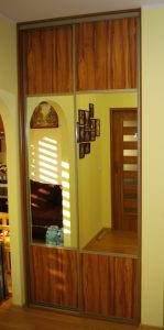 Wąska szafa wnękowa z drzwiami suwanymi w obramowaniu stalowym firmy Indeco, drzwi suwane to połaczenie płyty laminowanej i lustra srebrnego