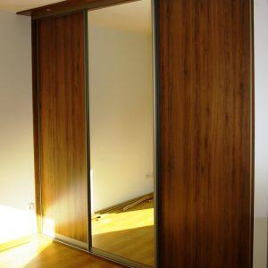 Szafa wnękowa z drzwiami suwanymi z wypuszczonym panelem oświetleniowym na górze, drzwi w obramowaniu aluminiowym