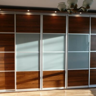Szafa wnękowa z obniżanym sufitem, drzwi to połączenie płyty laminowanej i szkła mlecznego, oświetlenie w cokole na górze szafy