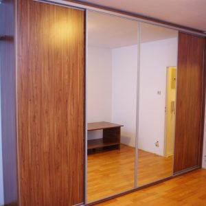 Szafa wolnostojąca z drzwiami suwanymi, drzwi w okuciach stalowych, skrzydła suwane wykonane z płyty laminowanej i lustra srebrnego