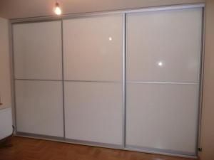 Szafa wnękowa z trzeba szerokimi drzwiami suwanymi, drzwi w obramowaniu aluminiowym firmy Indeco, wypełnienie to szkło lacobel