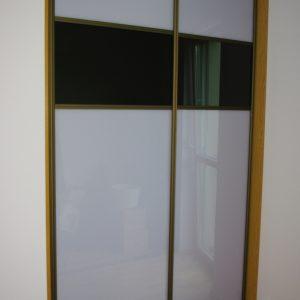 Szafa wnękowa z drzwiami suwanymi z obramowanie w kolorze oliwka, na drzwiach połączenie szkła lacobel