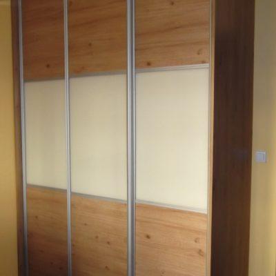 Szafa na wymiar w nie wielkim przedpokoju, drzwi suwane wykonane z połaczenia płyty laminowanej i szkła lacobel okute w obramowanie aluminiowe firmy Indeco