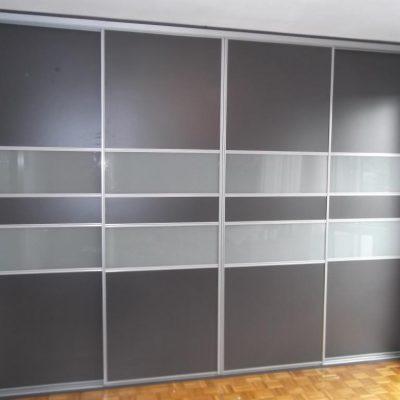 Szafa wnekowa w sypialni, drzwi w obramowaniu aluminiowym, połaczenie szkła mlecznego i płyty laminowanej