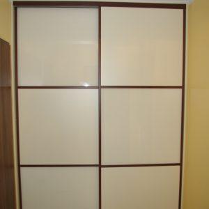 Szafa wnękowa w przedpokoju, obramowanie stalowe firmy Indeco w okleinie machoń, na drzwiach połączenie płyty laminowanej i szkła lacobel