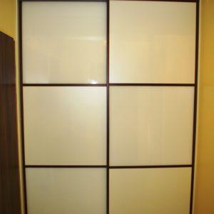 Szafa wnękowa, drzwi w obramowaniu stalowym w oklinie machoń, wypełnienie drzwi to połączenie płyty i szkła lacobel