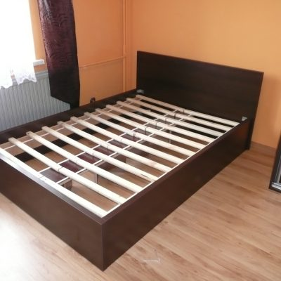 Łózko na wymiar, wykonane w całości z tej samej płyty co szafa z drzwiami suwanymi stojąca obok łóżka