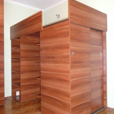 Łóżko na wymiar umiejscowione na szafie z drzwiami suwanymi oraz otwartymi regałami na książki
