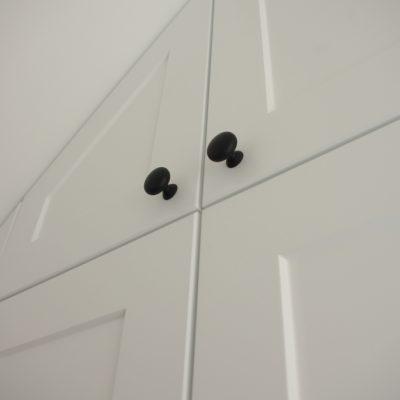 Fronty z MDF frezowanego w szafie na wymiar z uchwytem czarna gałka