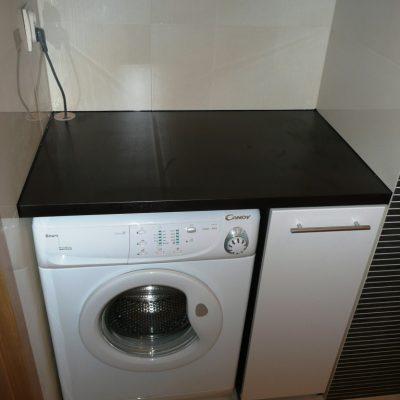 Zabudowa w łazience z koszem na bieliznę obok pralki