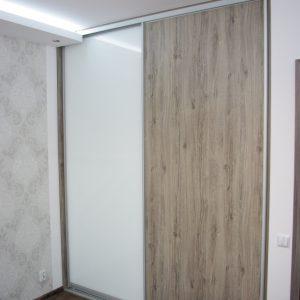 Szafa wnękowa w sypialni, drzwi przesuwne to połączenie białego szkła lacobel i płyty laminowanej