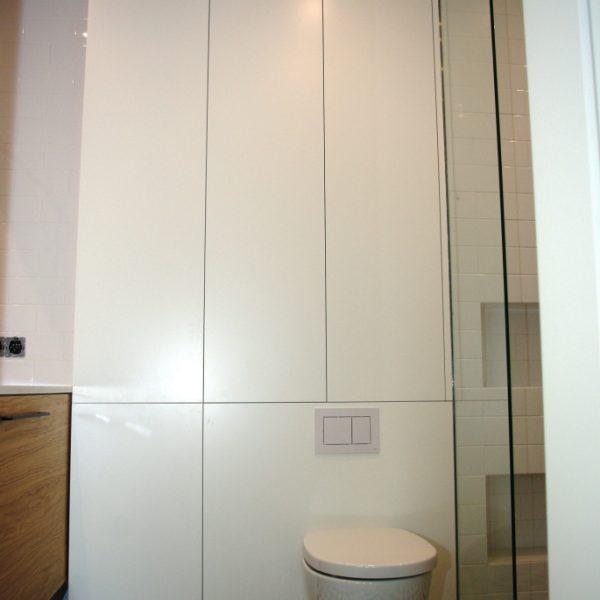 Zabudowa w łazience, panel MDf maskujący zabudowę toalety, fronty z MDF lakierowanego na biały mat, otwieranie tip-on
