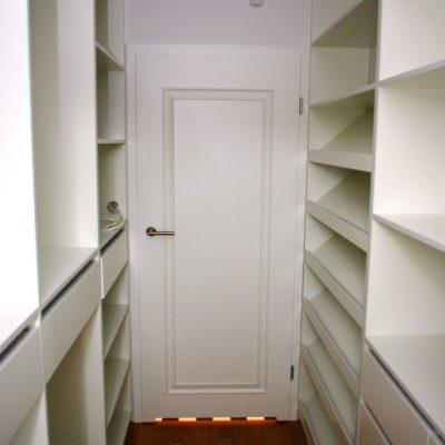 Wąska garderoba na zamówienie z półkami skośnymi na buty, szufladami, otwartymi półkami na ubrania oraz przestrzenią na ubrania wiszące