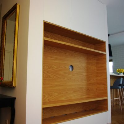 Zabudowa w salonie z forniru, od dołu szuflady z mechanizmem tip-on, górne fronty otwierane za pomocą tip-on
