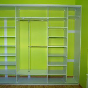 Wnętrze szafy wnękowej, szerokie półki podparte wstawkami z płyty, w cześci na ubrania wiszące automatyczne oświetlenie ledowe