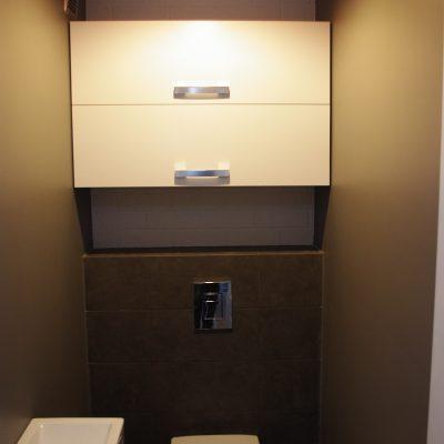 Szafka w toalecie z frontami unoszonymi do góry, fronty wykonane z MDF lakierowanego na biały mat