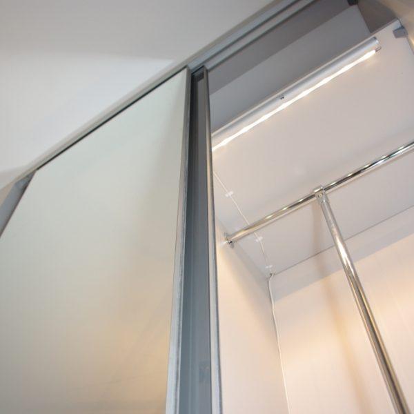 Drzwi suwane bez ramki w szafie wnękowej z oświetleniem