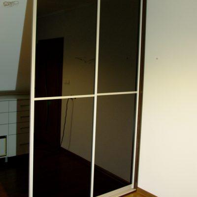 Zabudowa garderoby z drzwiami suwanymi z czarnym szkłem lacoebl