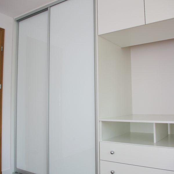 Zabudowa na wymiar w sypialni, drzwi suwane ze szkłem lacobel