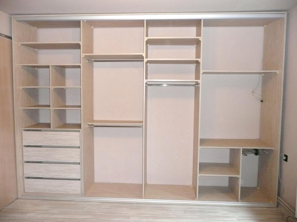 Wnętrze szafy wnękowej w sypialni, 4 duże szuflady na bieliznę, miejsce na telewizor schowany za drzwiami w szafie, wieszak na spodnie oraz półki i drązki na ubrania wiszące